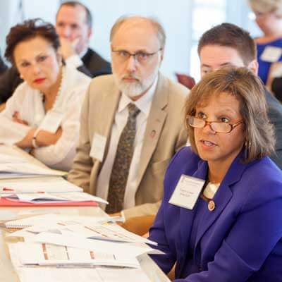 Congresswoman Robin Kelly (right) asks a question during Monday's Research Roundtable. NIU President Doug Baker, along with Board of Trustees Chair John Butler (behind Kelly) and immediate past chair Cherilyn G. Murer (left) led the event.