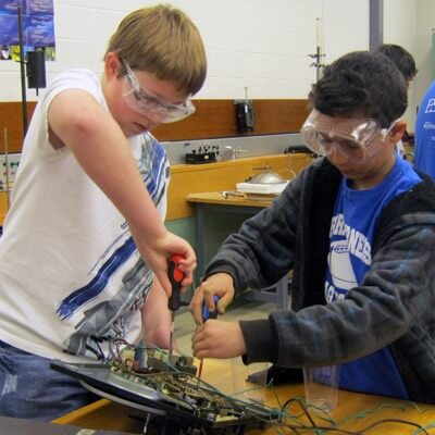Photo of two boys disassembling something electronic