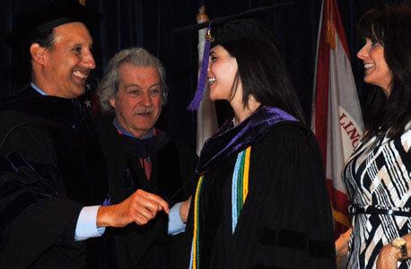 NIU Law faculty Robert Jones (far left) and Associate Dean David B. Gaebler (second from left) helped Donna Sandacz hood her duaghter, Shaina Kalanges.