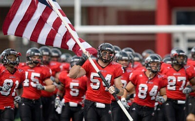 Jake Coffman (54) carries the U.S. flag onto Brigham Field.