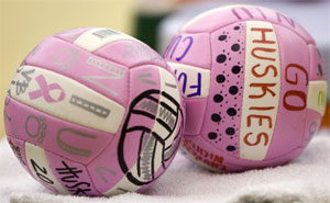 """A photo of pink """"Go Huskies"""" volleyballs"""