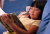 Photo of young girl reading book