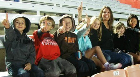 Erin Arnold (third from right) and some of her third- and fourth-grade students watch an on-field rehearsal of the Huskie Marching Band.
