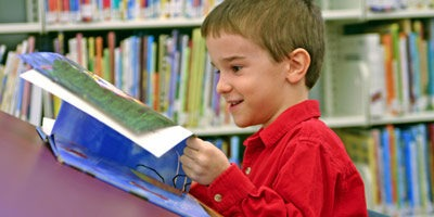 Photo of young boy reading in library
