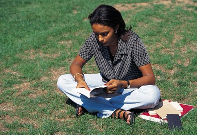 Photo of student studying on lawn