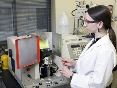 Photo of an NIU student conducting research in a lab.