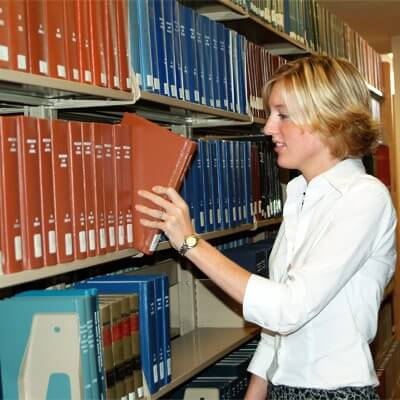 A photo of a student looking for books at the David C. Shapiro Memorial Law Library
