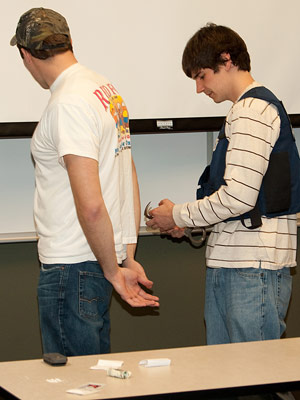 "NIU accountancy major Jonathan Strevell (right) ""arrests"" graduate student Gregory Broughton as part of a role-playing project conducted in the NIU College of Business by the Criminal Investigations arm of the IRS."