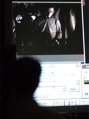 NIU percussion professor Greg Beyer (on screen and in silhouette) performs in a 2007 Alaskan concert from inside the NIU Music Building.