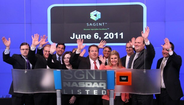 NIU alum Jeff Yordon (center), his wife, Kimberly (right), and colleagues wave after the Sagent Pharmeceuticals, Inc., CEO rang the closing bell at NASDAQ MarketSite. Photo from www.nasdaq.com.