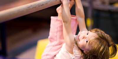 Photo of young girl on gymnastics parallel bar