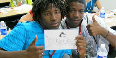 A student shows off the Huskie he drew to adorn the cover of his Health Careers scrap book.