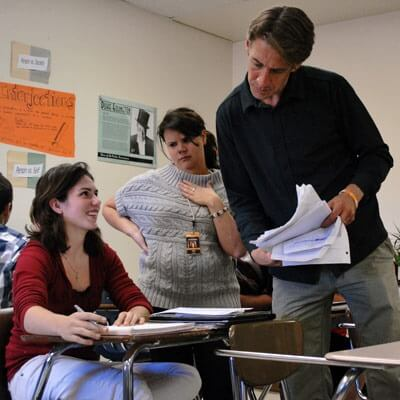 Fred Heuschel, who teaches humanities and media literacy at DHS, and his co-teacher speak with a student about her classwork.