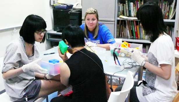 Former NIU undergraduate Joanna Ripstein, of Elmhurst, center, administers a hearing test to a student in Hong Kong during a recent visit lead by NIU audiology professor King Chung.