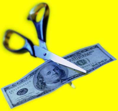 Photo of scissors cutting $100 bill