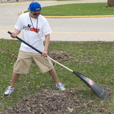 Photo of an NIU student raking during NIU Cares Day