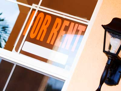 """Photo of a """"For Rent"""" sign inside a glass-paned door"""