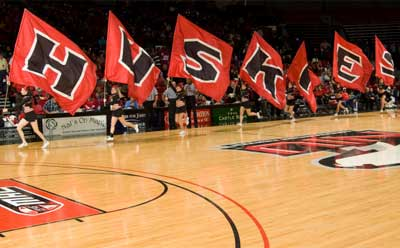 NIU cheerleaders run basketball court with H-U-S-K-I-E-S flags