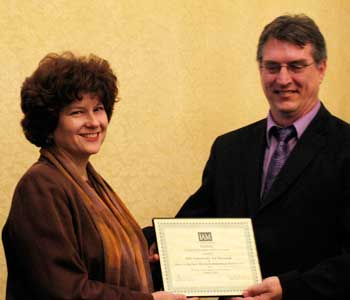 Jo Burke, director of the NIU Art Museum, accepts an award from David Becker, president of the board of directors of the Illinois Association of Museums.
