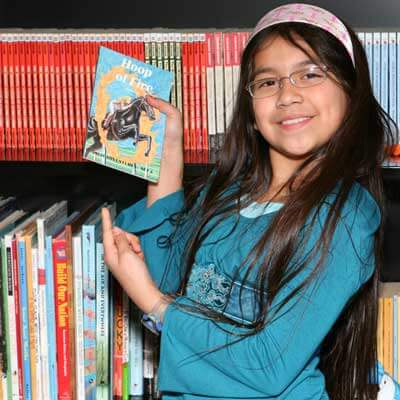 Photo of a young girl in a library pointing to a book