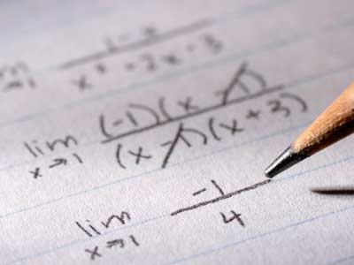 Photo of math problems on paper and pencil tip