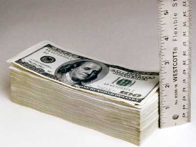 Stack of money next to ruler
