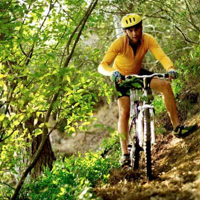 Photo of a man on a bike in the wooded hills