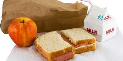 Photo of a brown bag lunch: sandwich, apple and milk