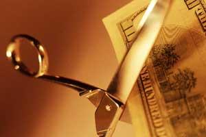 Photo of scissors cutting a $100 bill