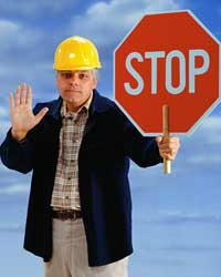Photo of a man holding a STOP sign