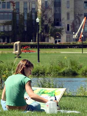 An NIU student paints at the East Lagoon.