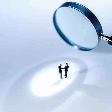 Photo of two men under the glare of a magnifying glass