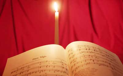 "Photo of ""Silent Night"" sheet music illuminated by candlelight"
