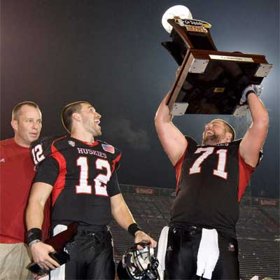 Scott Wedige hoists the trophy while Dave Doeren and Chandler Harnish look on.