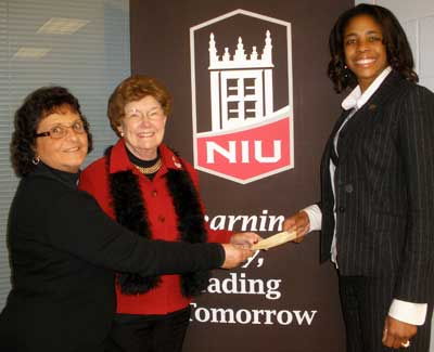 Joyce Angotti (left) and Sally Stevens (center) present a check to Coach Teaberry on behalf of the UWC board.