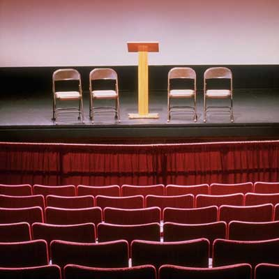 Photo of an auditorium with four chairs and a lectern on the stage