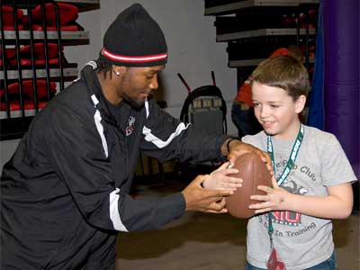 Jas Hopkins shows a young fan how to hold the ball.