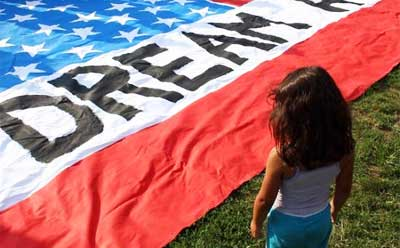 Photo of a young girl looking at a DREAM Act banner