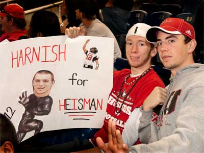 """Photo of two Huskies fan with """"Harnish for Heisman"""" sign"""