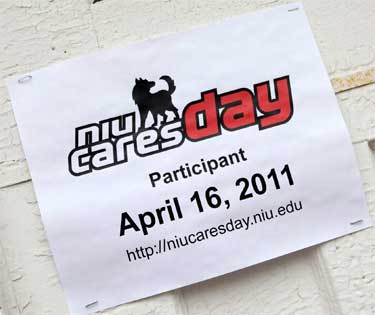 Photo of an NIU Cares Day 2011 sign stapled to wall