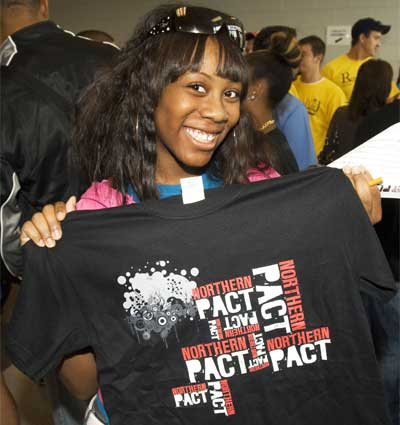 Photo of an NIU student with a Northern PACT T-shirt