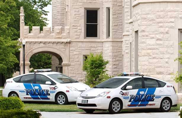A photo of two NIU police cars – Toyota Prius models – parked outside Altgled Hall.