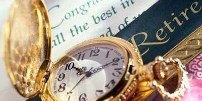 Photo of gold pocket watch and retirement greeting card