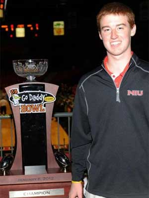 An NIU Huskies fan poses with the GoDaddy.com Bowl trophy.