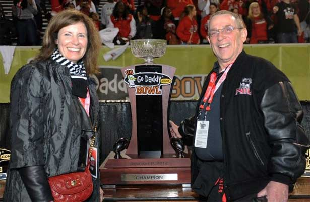NIU Huskies fans pose with the GoDaddy.com Bowl trophy