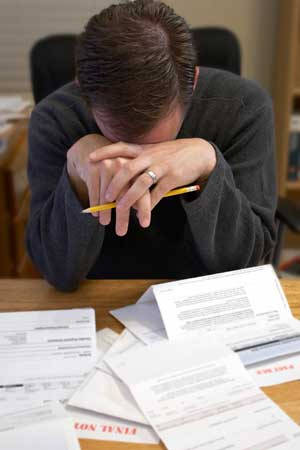 Photo of a man hanging his head over a pile of unpaid bills