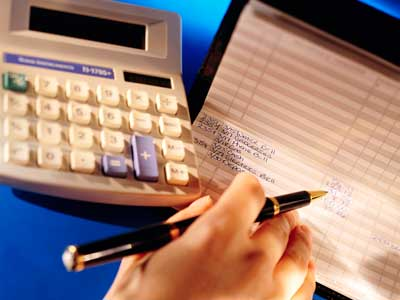Photo of a calculator, checkbook and hand holding a pen