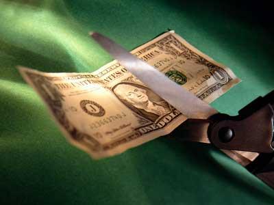 Photo of a pair of scissors cutting a $1 bill