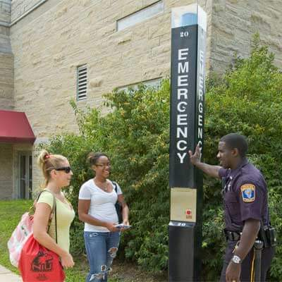 An NIU police officer speaks with students next to an emergency call box.