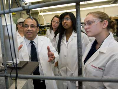 NIU chemist Narayan Hosmane, who is participating in the REU program, works with students in his lab.